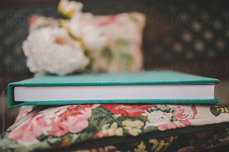 Pretty vintage  green photo book detail laying on a floral cushion by Sanja (Lydia) Kulusic for Stocksy United