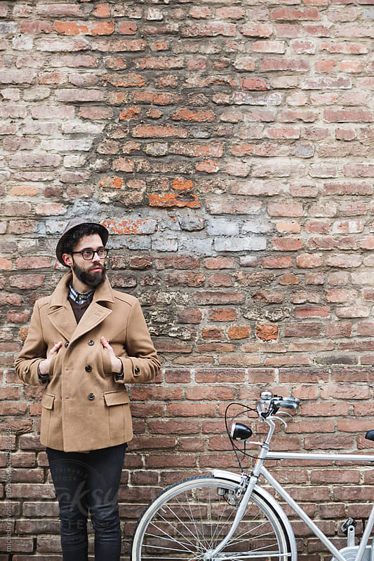 Man standing near his bike by michela ravasio for Stocksy United