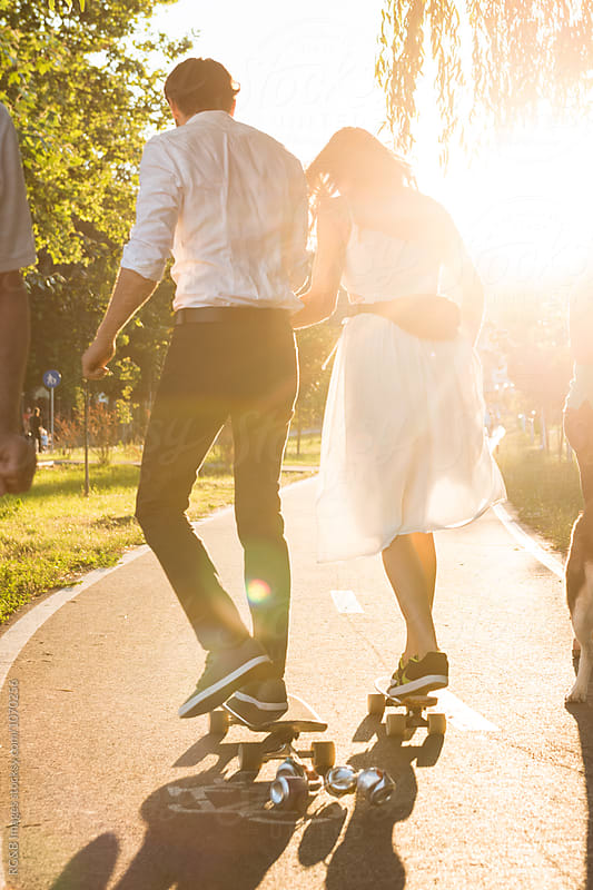 Just married couple on skateboards by RG&B Images for Stocksy United