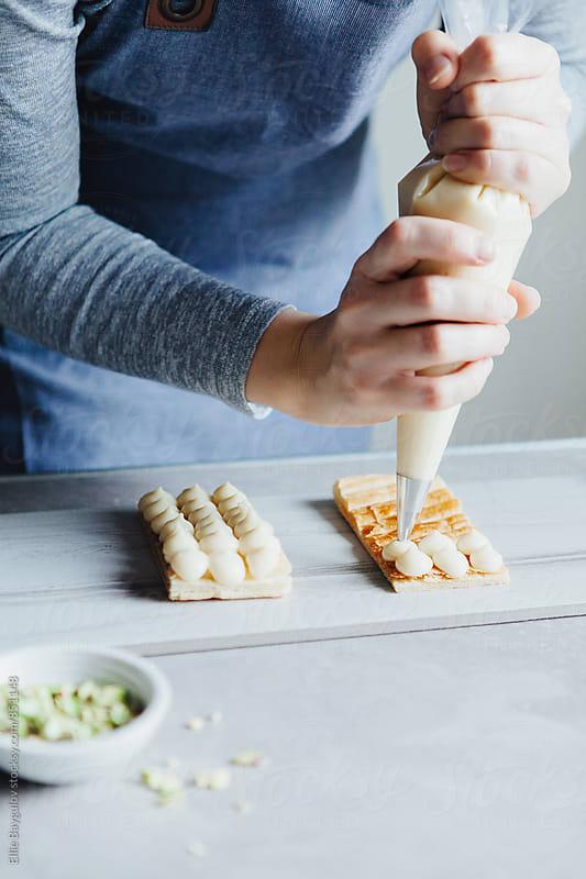 Woman preparing vanilla millefeuille by Ellie Baygulov for Stocksy United