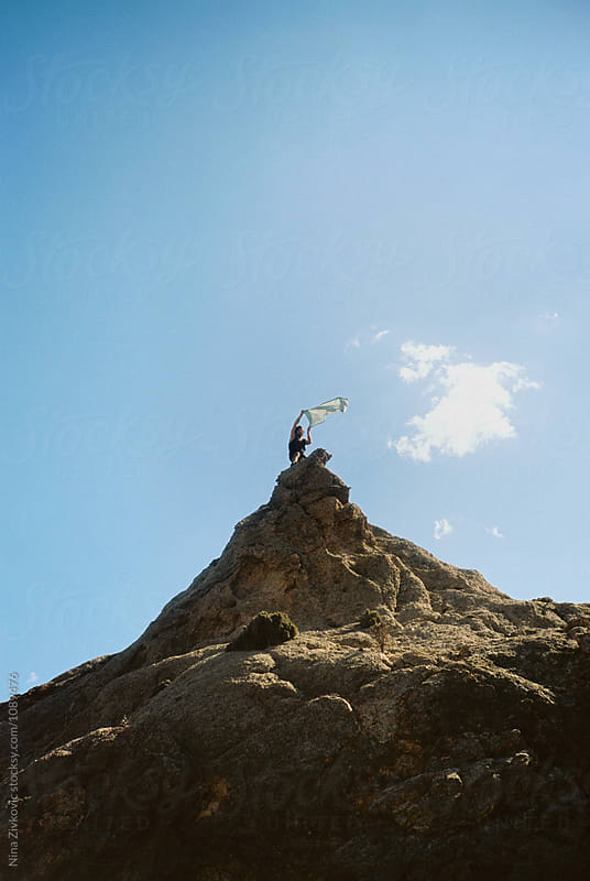A young man climbed the high rock, waving behind it. by Nina Zivkovic for Stocksy United
