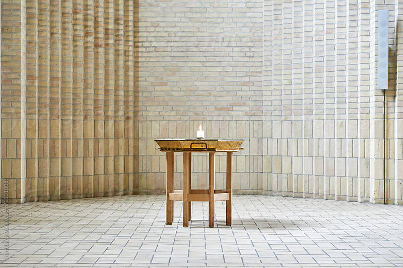 Church candle lightning on table in white brick room by Trent Lanz for Stocksy United