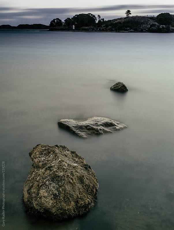 Three rocks in a lake by Gary Radler Photography for Stocksy United