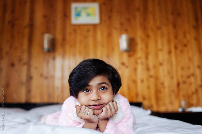 Portrait of thoughtful little girl lying on bed by Saptak Ganguly for Stocksy United