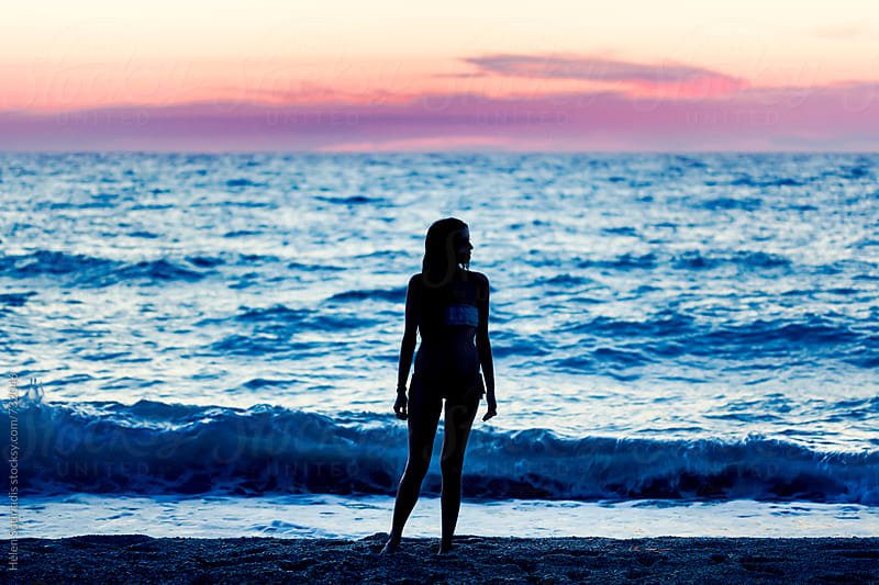 Young Woman Stands on the Shore at Twilight by Helen Sotiriadis for Stocksy United