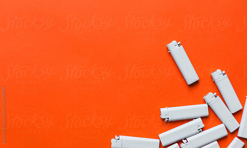 Pile of white lighters on orange/red background. by Audrey Shtecinjo for Stocksy United