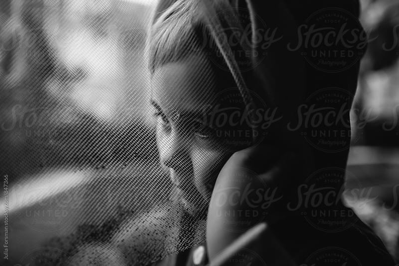 A little girl hides her face behind an old net curtain. by Julia Forsman for Stocksy United