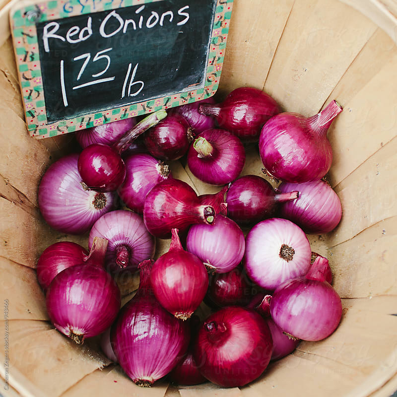 red onions in basket at farmers market by Cameron Zegers for Stocksy United