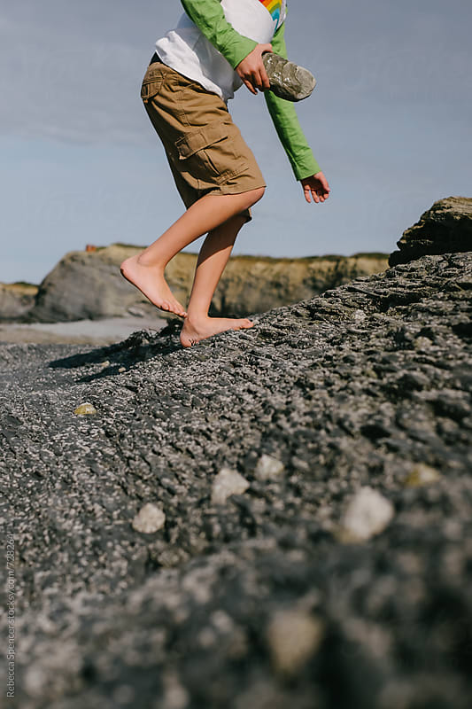 Bare footed child walking on rocks by Rebecca Spencer for Stocksy United
