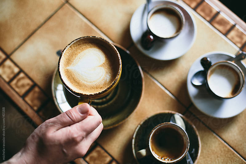 A hand lifts a cup of cappuccino. by michela ravasio for Stocksy United