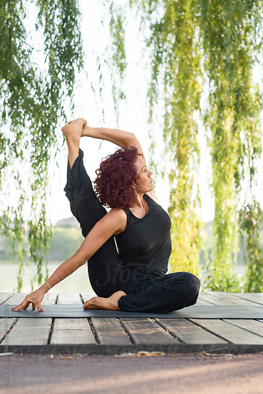 Mature woman practicing yoga stretching outdoor by RG&B Images for Stocksy United