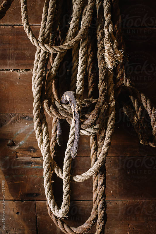 old rope and horse shoes in barn by Jesse Morrow for Stocksy United