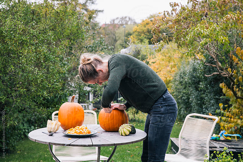 Woman carving pumpkin for Halloween in the garden by Lior + Lone for Stocksy United