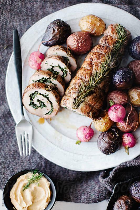 Stuffed herb pork tenderloin  by Ellie Baygulov for Stocksy United