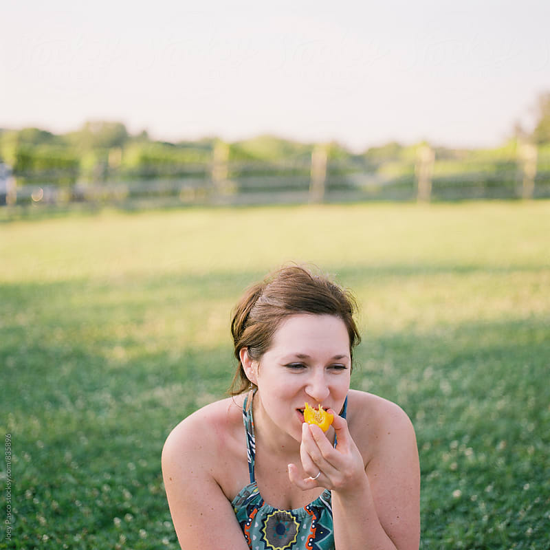 Woman laughing while biting into a vegetable at a vineyard picnic on a summer evening by Joey Pasco for Stocksy United