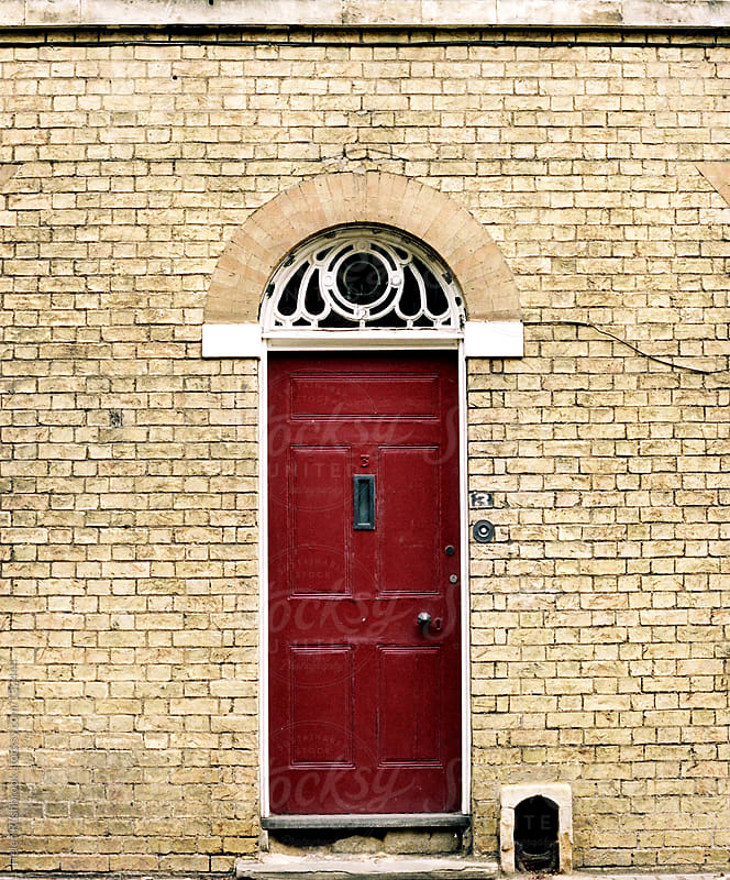 A red door by Helen Rushbrook for Stocksy United