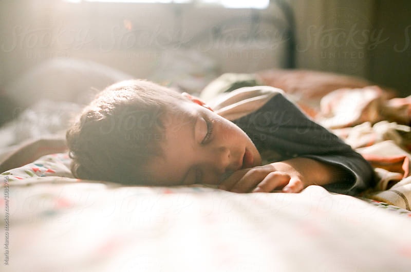 sunfilled photo of boy sleeping by Maria Manco for Stocksy United