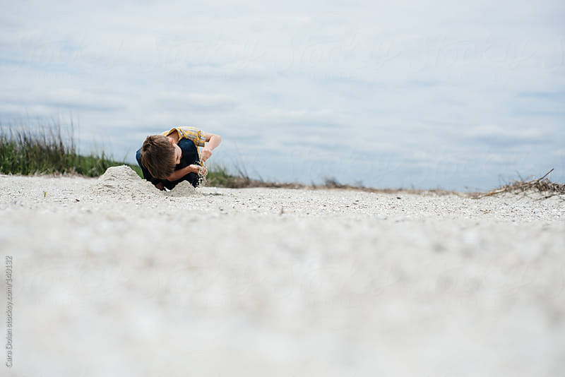 Young boy plays alone on a beach by Cara Dolan for Stocksy United