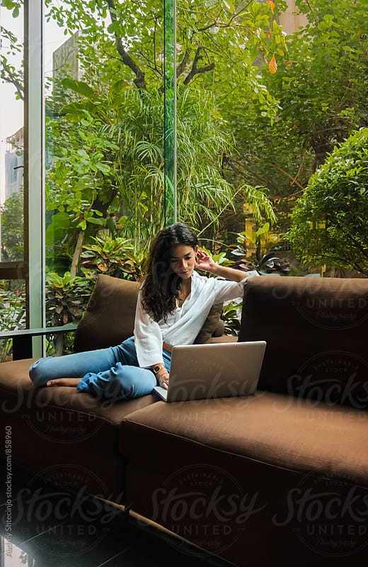 Attractive teenage female using her laptop on sofa with vew on big garden in background. by Marko Milanovic for Stocksy United