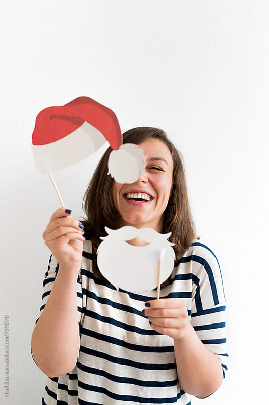 Laughing young woman in Santa disguise  by Pixel Stories for Stocksy United