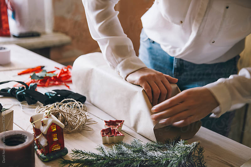 Woman wrapping Christmas present by Danil Nevsky for Stocksy United