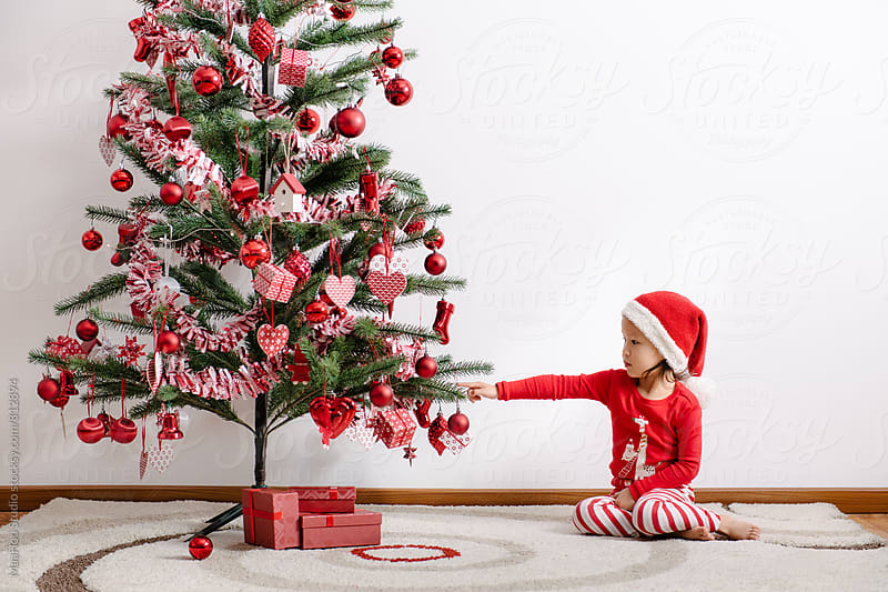 Cute toddler girl touching christmas tree by MaaHoo Studio for Stocksy United