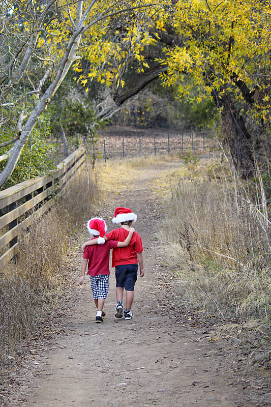 Two boys walking down nature path in Christmas hats by Monica Murphy for Stocksy United