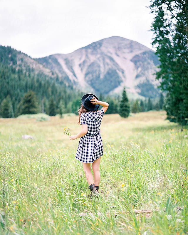Woman holding onto hat in meadow by Daniel Kim Photography for Stocksy United