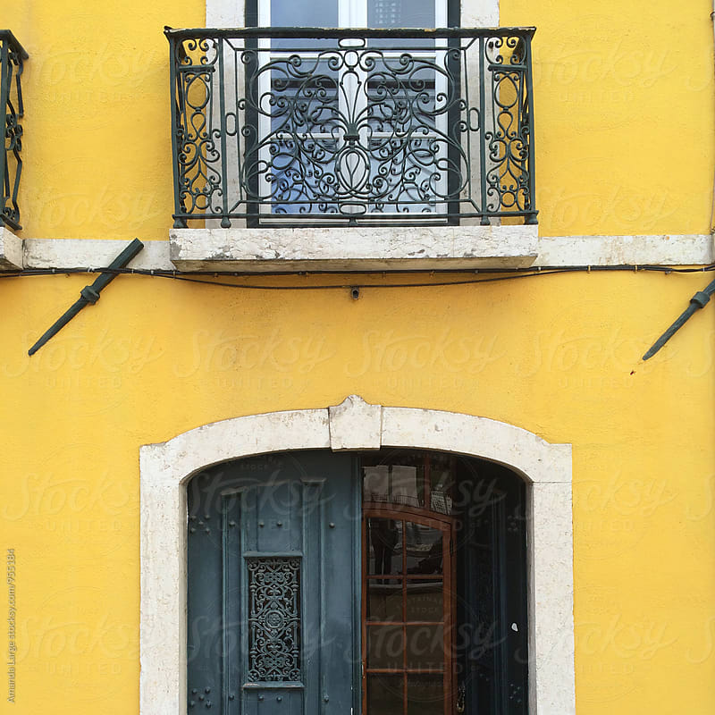 Yellow building facade with a window balcony in Lisbon, Portugla by Amanda Large for Stocksy United