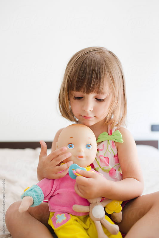 Cute little girl stroking her doll by michela ravasio for Stocksy United