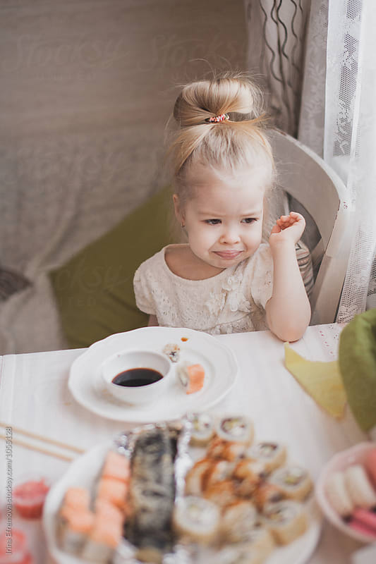 Frustrated little girl with a plate of sushi by Irina Efremova for Stocksy United