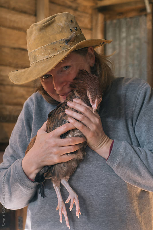 Woman holding chicken by Rowena Naylor for Stocksy United