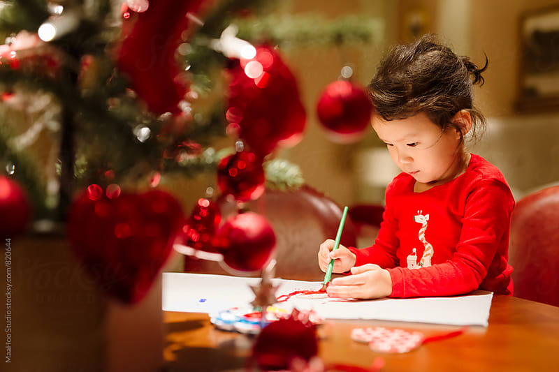 Cute girl painting on christmas by Maa Hoo for Stocksy United
