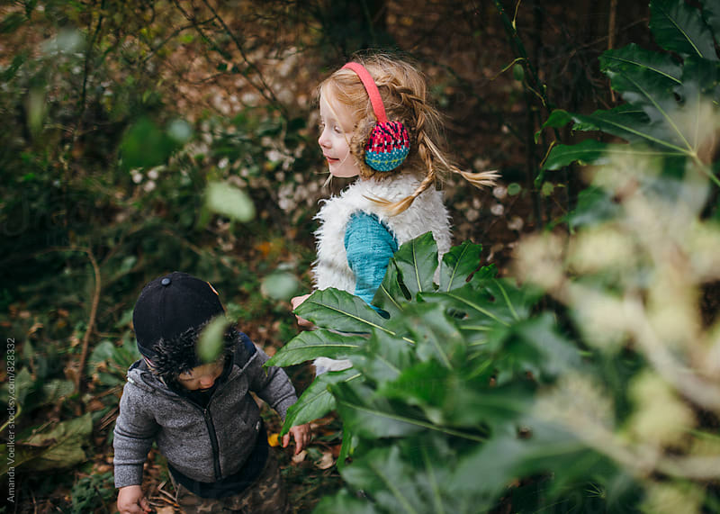 Little Girl and Her toddler Brother Deep in the Overgrown Garden by Amanda Voelker for Stocksy United