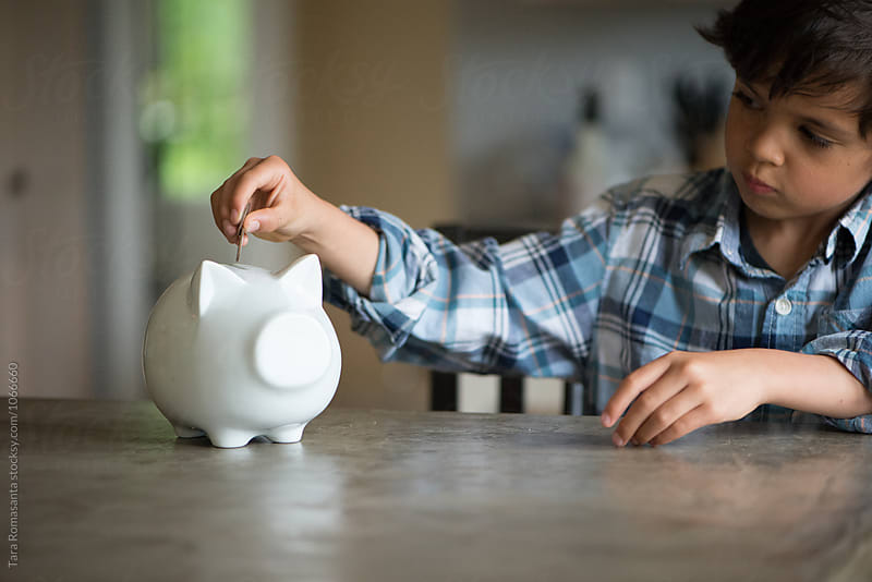 child puts coins in a piggy bank by Tara Romasanta for Stocksy United