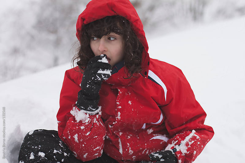 Girl eating the white snow by Beatrix Boros for Stocksy United