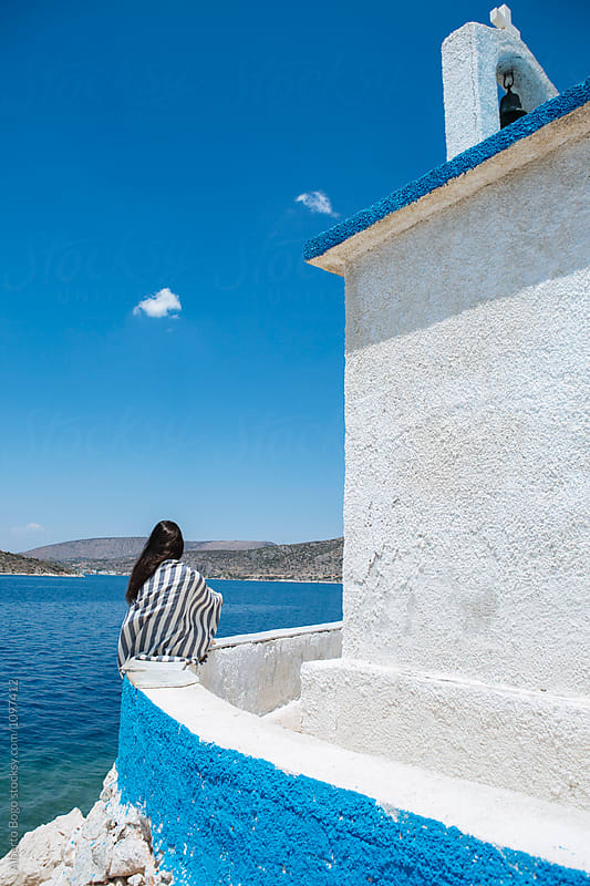 Unrecognizable black-haired tourist sitting at Greek building at sea by Alberto Bogo for Stocksy United