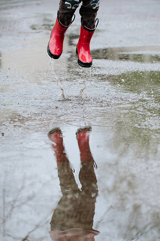 girl jumping in rain puddle by Brian Powell for Stocksy United