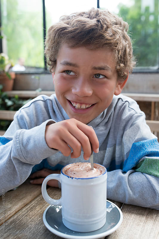 Boy smiling while drinking hot cocoa by Trent Lanz for Stocksy United