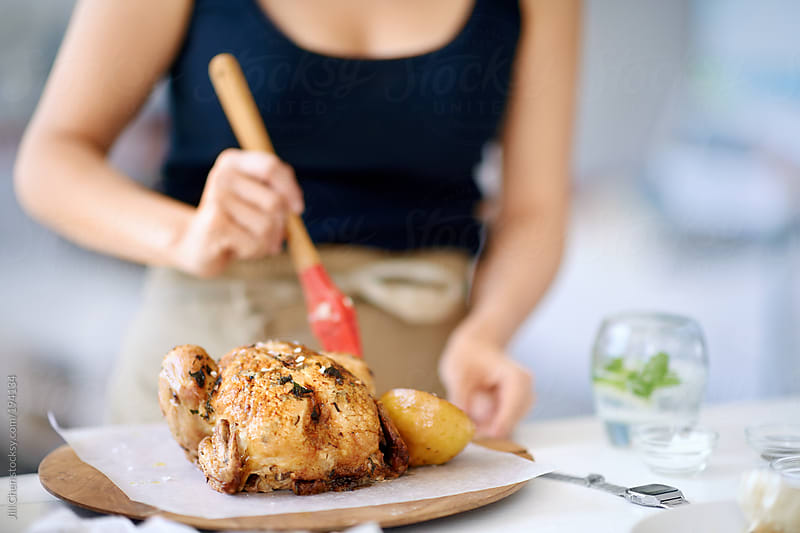 Woman cook preparing to serve a roast chicken  by Jill Chen for Stocksy United