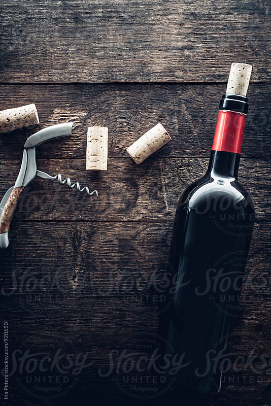Bottle of wine, corks and grapes on wooden background by Ina Peters for Stocksy United