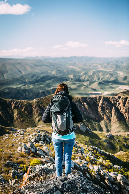 Female hiker with backpack on a mountain summit enjoying the view by Micky Wiswedel for Stocksy United