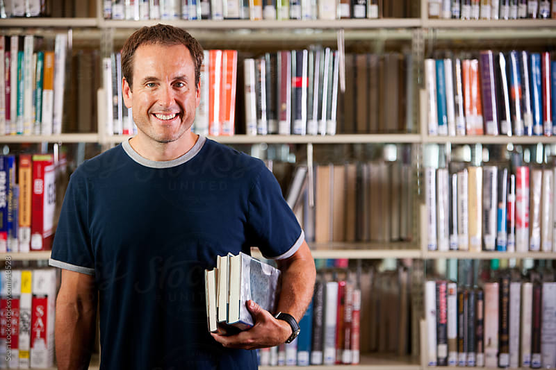 Library: Happy Man with Stack of Books by Sean Locke for Stocksy United