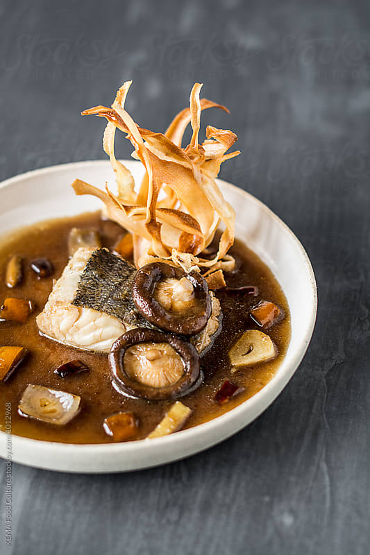 Braised hake with chinese wine , shitakes and crispy yuca  by KEMA Food Culture for Stocksy United