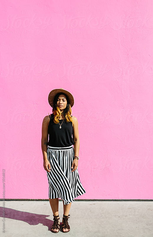 A young woman standing by a hot pink wall.  by Kristen Curette Hines for Stocksy United