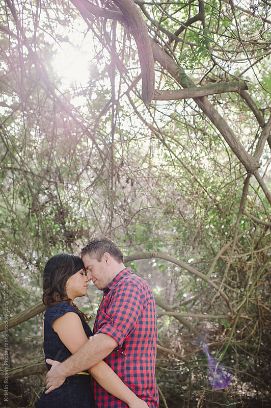 Romantic couple snuggling in nature by Kristin Rogers Photography for Stocksy United