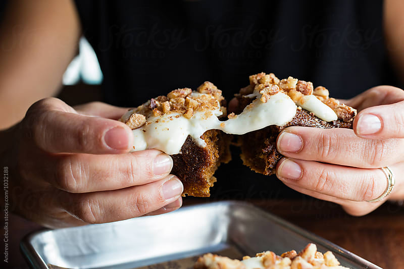 Hands pulling apart a dessert pastry by Andrew Cebulka for Stocksy United
