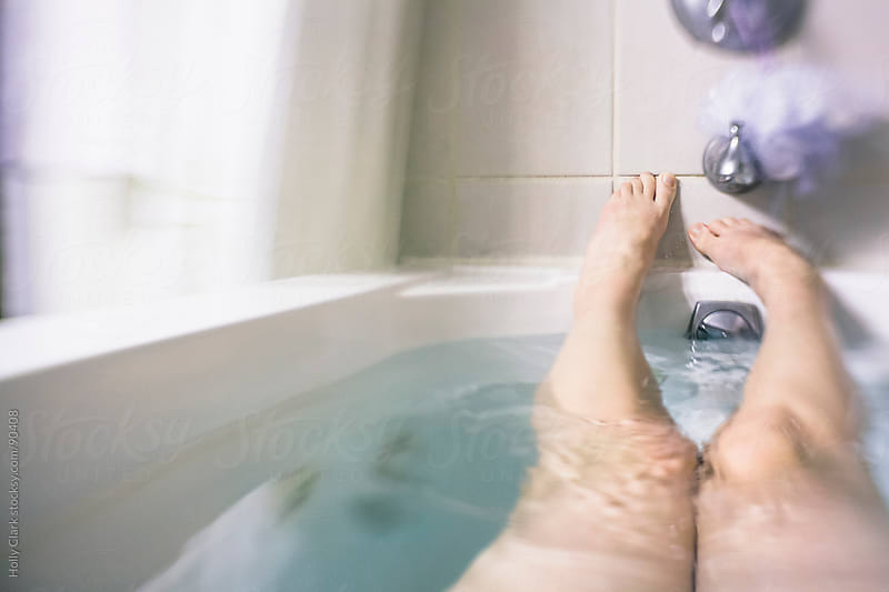 A woman's legs and feet in a bathtub. by Holly Clark for Stocksy United