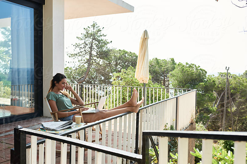 Relaxed woman using laptop on balcony by Guille Faingold for Stocksy United