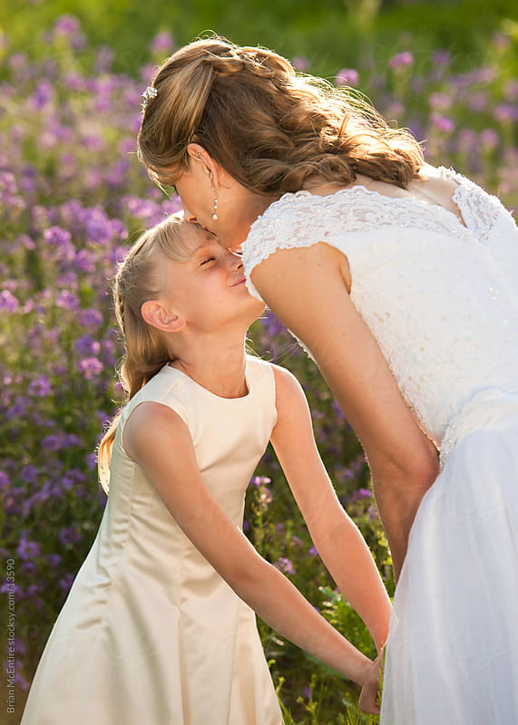 Bride: Mother Kisses her Daughter Flower Girl by Brian McEntire for Stocksy United